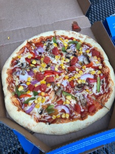 Domino's pizza topped with vegan cheese and lots of sweetcorn, tomato cubes, green and red pepper, red onion, and mushrooms.