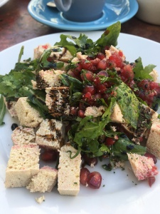 Close up of rocket and tofu salad with a balsamic drizzle and pomegranate seeds on top.