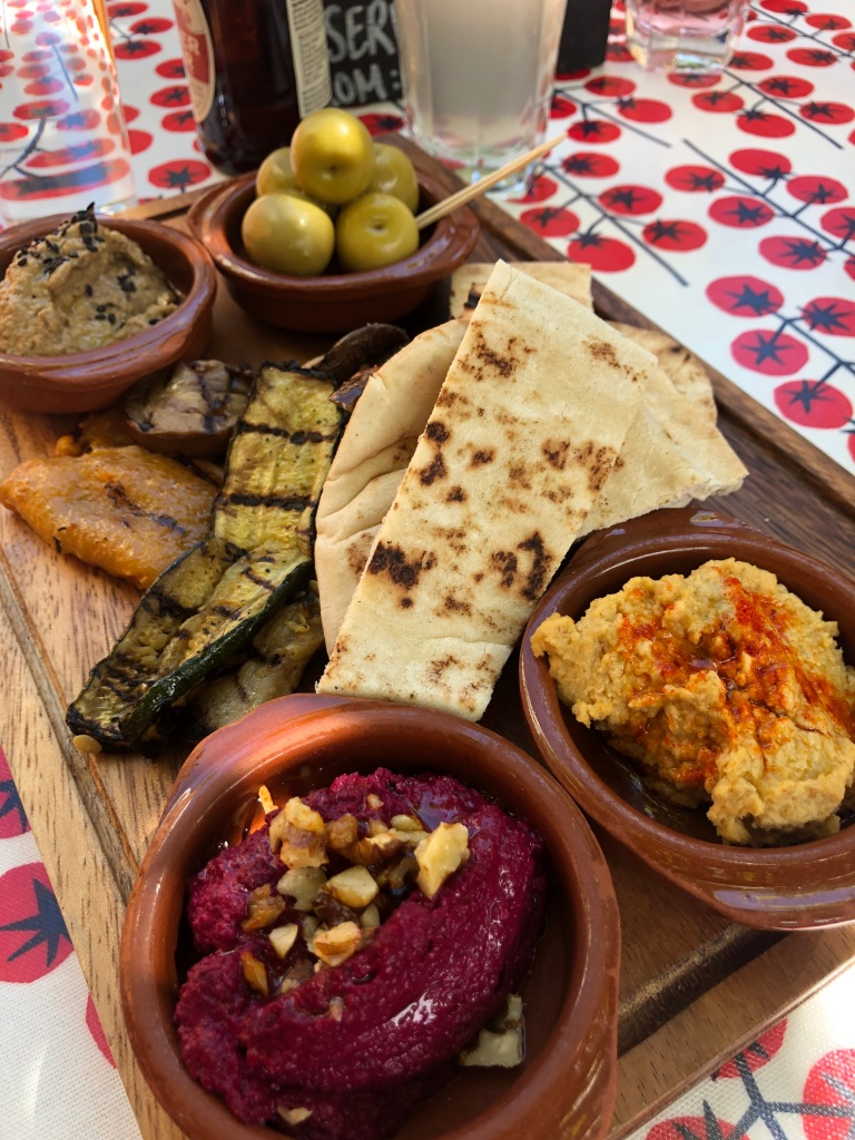 Vegan mezze board from The Punter pub in Oxford featuring beetroot houmous, classic houmous, baba ganoush, olives, grilled vegetables and pita bread.