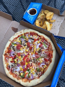 small box of potato wedges and barbecue sauce, next to a large box with a vegan pizza in