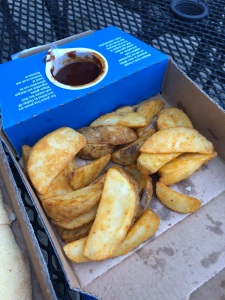 Domino's potato wedges in a box with a small pot of barbecue sauce on the side