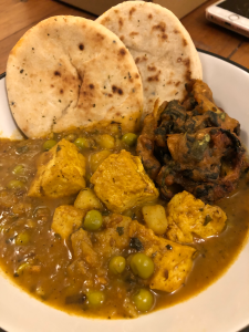 Medium sized bowl full of food. At the front, a pile of tofu and peas. At the back, two mini naan breads and an onion bhaji.