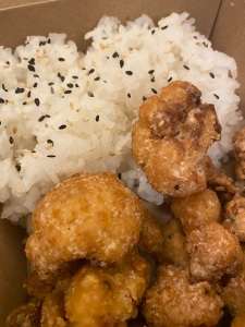crispy coated cauliflower bites with pile of rice topped with black sesame seeds