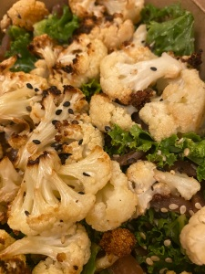bowl of cauliflower, some chargrilled bits. kale poking through the gaps, all topped with black sesame seeds.