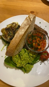 Plate with toast standing upright in centre. on the left, ball of fried mashed potato. On the right, a small glass dish with baked beans in topped with chives; one roasted vine tomato, one sausage visible and pile of smashed avocado on spinach leaves.