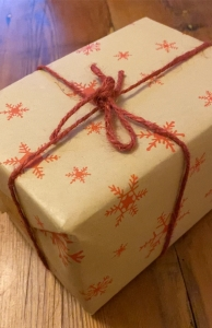 Small cuboid parcel wrapped in brown paper with red snowflake pattern, tied with red string
