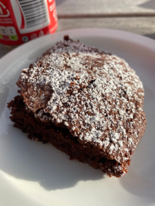 corner piece of brownie with heavy dusting of icing sugar on top