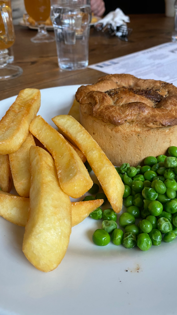 White plate with large chips and small portion of peas at the front, brown rustic looking pie at the back.